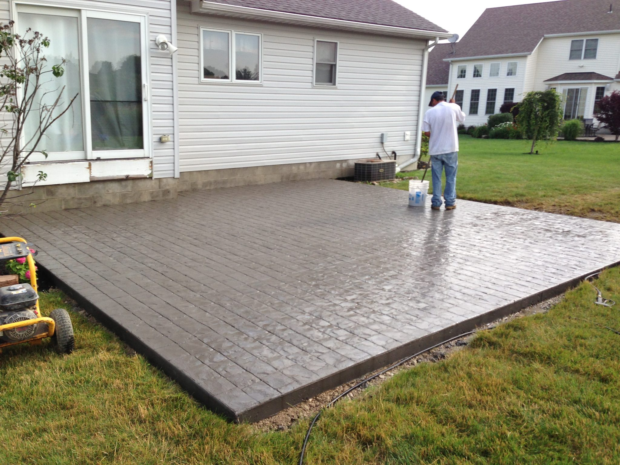 Patio ideas for backyard with wrought iron patio furniture black and red sunbrella on cool stamped concrete patio flooring